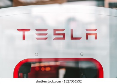 MILAN, ITALY - FEBRUARY 07, 2019: Tesla logo on supercharger. Car store in Piazza Gae Aulenti square in Milan, Italy