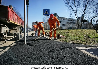 Milan, Italy - February 13, 2014: Asphalt workers with shovels patching asphalt during road repairing works.