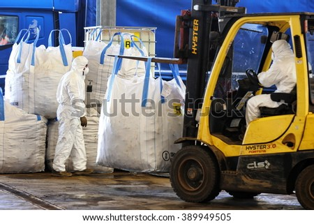 Milan, Italy - February 2016: men at work in a center of asbestos storage