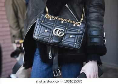 Milan, Italy - February 21, 2018: Girl with a Gucci purse during Milan Fashion Week shows.