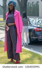 Milan, Italy - February 21, 2019: Model wears a long striped dress, a fuchsia overcoat and a headdress during the Armani fashion show for the autumn / winter 2019-2020 collection