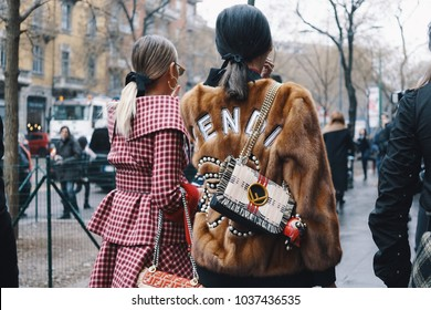 Milan, Italy - February 22, 2018: Fashionable girls wearing Fendi clothing posing after Fendi fashion show during Milan Fashion Week - street style concept