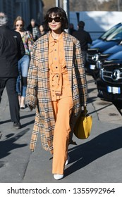 Milan, Italy - February 22, 2019: Street style – Woman wearing a Burberry coat after a fashion show during Milan Fashion Week - MFWFW19