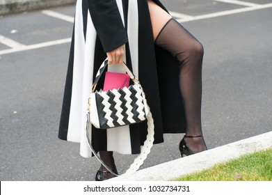 MILAN, ITALY - FEBRUARY 24, 2018: Stylish person posing stocking shoes outside Armani during Milan Fashion Week Fall/Winter 2018/19 on February 24, 2018 in Milan, Italy.
