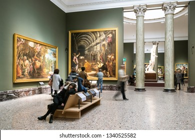 MILAN, ITALY - FEBRUARY 24, 2019: tourists sit in hall in Pinacoteca di Brera (Brera Art Gallery) in Milan. The Brera is national picture gallery of ancient and modern art in Palazzo Brera