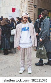 MILAN, ITALY - FEBRUARY 26, 2016: Fashionable man attending models and vips in the streets during Milan Fashion Week Women Fall/Winter 2015/2016
