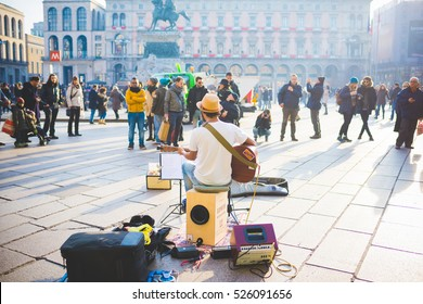 MILAN, ITALY - JANUARY 02, 2016: back view of street musician playing guitar in outdoor in Duomo Square in Milan, Italy