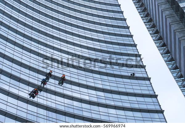 MILAN / ITALY - January 10, 2017: Window washers cleaning the glass facade of a Modern building in the new Porta Nuova district, in Milan, Italy