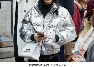 MILAN, ITALY - JANUARY 12, 2019: Woman with silver padded jacket and smartphone in hand before Frankie Morello fashion show, Milan Fashion Week street style
