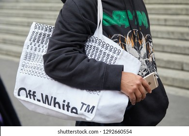 MILAN, ITALY - JANUARY 12, 2019: Man with white Off White bag and golden iPhone in hand before Frankie Morello fashion show, Milan Fashion Week street style