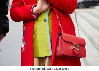 MILAN, ITALY - JANUARY 12, 2019: Woman with red coat and Gucci leather bag with golden chain before Frankie Morello fashion show, Milan Fashion Week street style