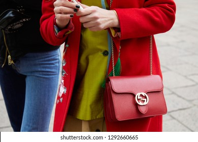 MILAN, ITALY - JANUARY 12, 2019: Woman with red Gucci leather bag and coat before Frankie Morello fashion show, Milan Fashion Week street style