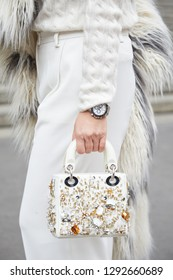 MILAN, ITALY - JANUARY 12, 2019: Woman with Dior white leather bag with golden details and Rolex Daytona watch before Frankie Morello fashion show, Milan Fashion Week street style