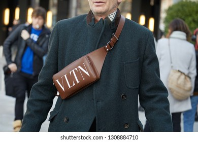 MILAN, ITALY - JANUARY 12, 2019: Man with brown leather Valentino pouch before Neil Barrett fashion show, Milan Fashion Week street style