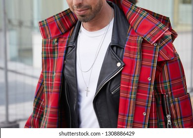 MILAN, ITALY - JANUARY 12, 2019: Man with red tartan coat and black leather jacket before Neil Barrett fashion show, Milan Fashion Week street style