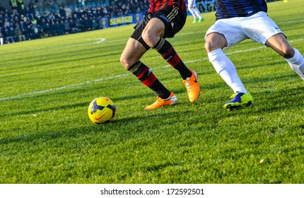 MILAN, ITALY - JANUARY 12 Youth italian soccer match in Milan January 12, 2014. A football players close up action with the green pitch on the background.