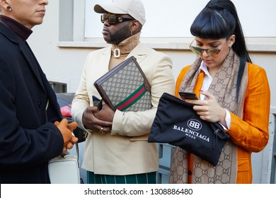 MILAN, ITALY - JANUARY 13, 2019: Woman with orange jacket and Balenciaga bag and man with Gucci bag before John Richmond fashion show, Milan Fashion Week street style