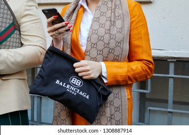 MILAN, ITALY - JANUARY 13, 2019: Woman with orange jacket, Balenciaga bag and Gucci scarf looking at smartphone before John Richmond fashion show, Milan Fashion Week street style