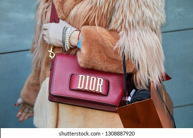 MILAN, ITALY - JANUARY 13, 2019: Woman with red leather Dior bag and brown fur coat before John Richmond fashion show, Milan Fashion Week street style