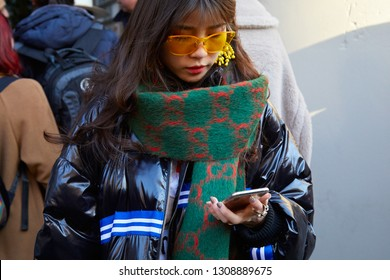 MILAN, ITALY - JANUARY 13, 2019: Woman with green and red Gucci scarf and orange sunglasses looking at smartphone before John Richmond fashion show, Milan Fashion Week street style
