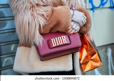 MILAN, ITALY - JANUARY 13, 2019: Woman with red leather Dior bag and brown pink fur coat before John Richmond fashion show, Milan Fashion Week street style