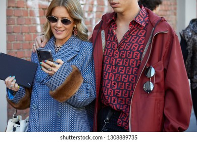 MILAN, ITALY - JANUARY 14, 2019: Woman and man with red and blue Fendi logo shirt walking before Fendi fashion show, Milan Fashion Week street style