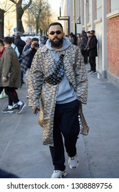 MILAN, ITALY - JANUARY 14, 2019: Man with Vetements beige trench coat and black leather MCM pouch before Fendi fashion show, Milan Fashion Week street style