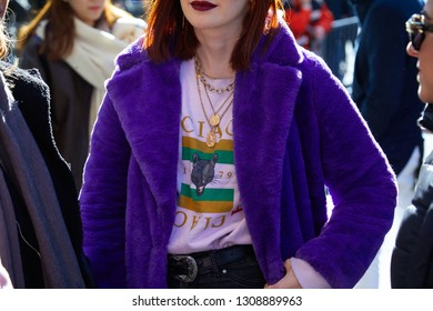 MILAN, ITALY - JANUARY 14, 2019: Woman with purple fur coat, pink Gucci shirt and golden necklace before Emporio Armani fashion show, Milan Fashion Week street style