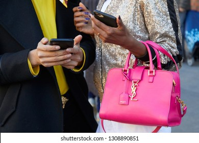 MILAN, ITALY - JANUARY 14, 2019: Woman with pink Yves Saint Laurent leather bag and golden sequin jacket before Fendi fashion show, Milan Fashion Week street style