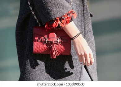 MILAN, ITALY - JANUARY 14, 2019: Woman with red Gucci leather bag and gray coat before Emporio Armani fashion show, Milan Fashion Week street style