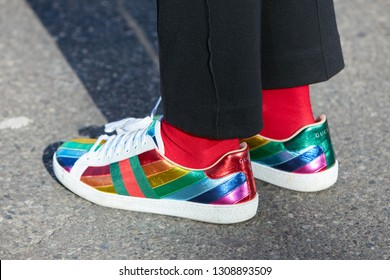 MILAN, ITALY - JANUARY 14, 2019: Woman with rainbow colors Gucci sneakers and red socks before Emporio Armani fashion show, Milan Fashion Week street style
