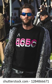 MILAN, ITALY - JANUARY 14: Fashionable man poses outside Armani fashion show during Milan Men's Fashion Week on JANUARY 14, 2019 in Milan.