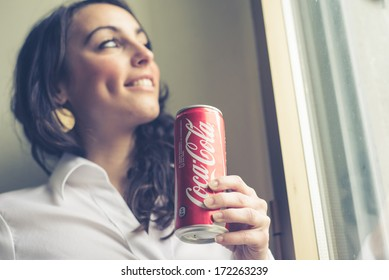 MILAN, ITALY - JANUARY 16, 2014: Beautiful woman drinking coca cola bottle can 33 cl. Coca Cola is the most famous brand soft drink in the world