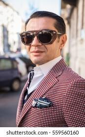 MILAN, ITALY - JANUARY 16: Fashionable man poses outside Etro fashion show building during Milan Men's Fashion Week on JANUARY 16, 2017 in Milan.