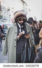 MILAN, ITALY - JANUARY 18: People gather outside John Richmond fashion show building for Milan Men's Fashion Week on JANUARY 18, 2015 in Milan.