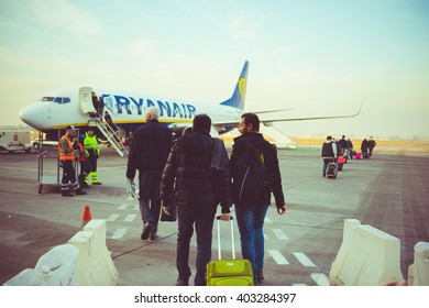 MILAN, ITALY - JANUARY 2, 2016: Back view of people carrying luggage boarding on a Ryanair plane. Ryanair is the biggest low-cost airline company in the world.