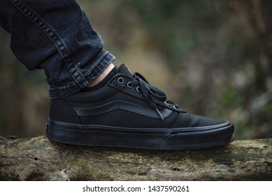 Milan, Italy - January 26, 2019: Young man wearing Vans Old Skool shoes in the wood - illustrative editorial