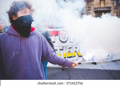 MILAN, ITALY - JANUARY 29: students demonstrating against racism, fascism and the meeting between Marie Le Pen and Matteo Salvini in Milan on January 29, 2016. A masked student holding a smoke pot.