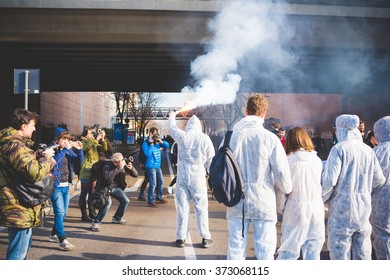 MILAN, ITALY - JANUARY 29: students protesting against meeting between Marie Le Pen and Matteo Salvini on Milan on January 29, 2016. Rear view of protestor wearing exterminator mask holding smoke pot