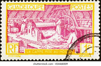 Milan, Italy - July 11, 2016: Processing of sugar cane on vintage postage stamp of Guadeloupe