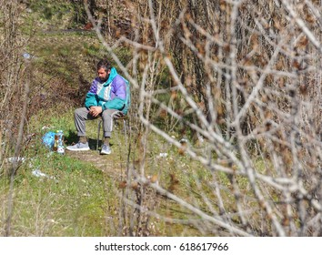 MILAN, ITALY - JULY 12, 2016: homeless man on the bench in the Bronx park after fighting for life.
