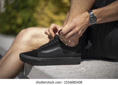 Milan, Italy - July 14, 2019: Young man wearing Vans Old Skool shoes and Adidas socks in the street - illustrative editorial