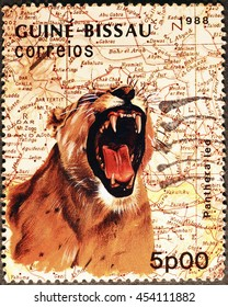 Milan, Italy - July 15, 2016: Roaring lioness on postage stamp of Guinea-Bissau
