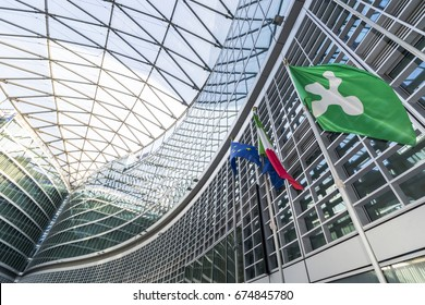 """MILAN, ITALY - July 2 2017; Flags waving at the entrance of the head office """"Palazzo della regione""""."""