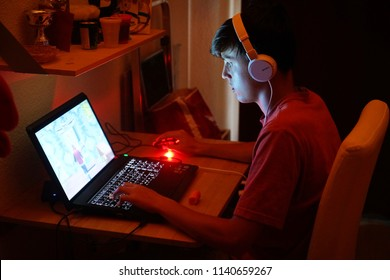 Milan, Italy - July 2018: Teenager playing Fortnite video game in the his bedroom by night.