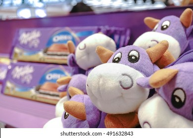 MILAN, ITALY - JULY 22, 2016 : Photo of Milka Chocolate Purple Cow Plush, a plie of toys pencil pouch plush for kids at duty free shop, in Milano Malpensa International Airport. Editorial Used Only.