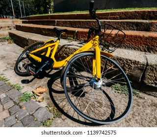 Milan, Italy - July 22, 2018: Close up of damaged tyre on yellow Ofo bike sharing Milan, a bike on the street. Founded in China, Ofo is the world s first and largest station-free bike sharing platform
