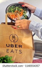 Milan - Italy , july 22,2018 - uber eats is an International food delivery company from U.S - home delivery of food - people order food and eat it at work