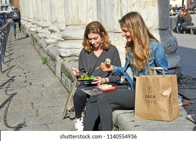 Milan - Italy , july 22,2018 - uber eats is an International food delivery company from U.S - home delivery of food - people order food and eat it outdoor