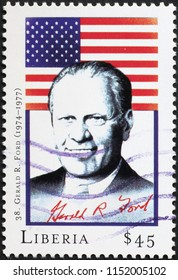 Milan, Italy - July 27, 2018: President Gerald Ford and flag on postage stamp
